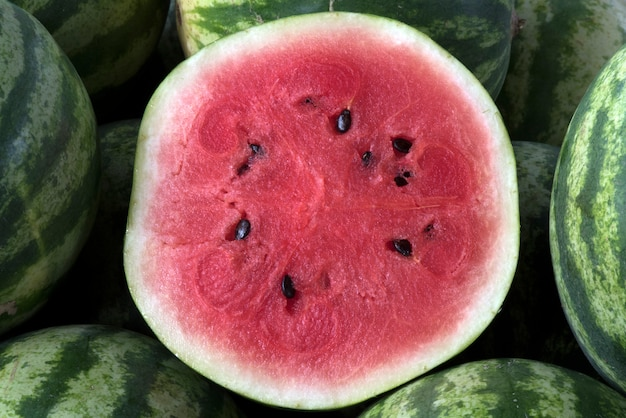 Sliced watermelon over heap of whole fruits