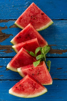 Sliced watermelon top view. many slices on an old rustic blue table. copy space. food backrgound.