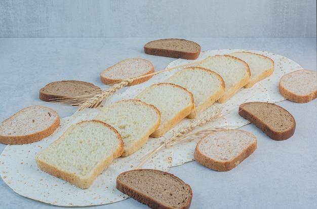 Нарезанный пшеничный и ржаной хлеб с лавашем на мраморном фоне. фото высокого качества