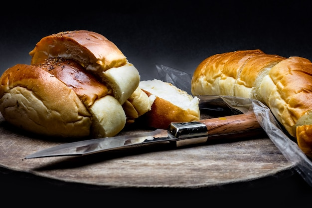Sliced wheat bread above a wooden chopping board with a knife on a dark rough texture background