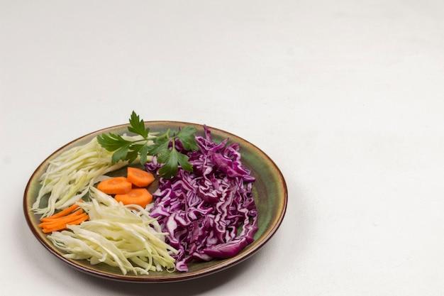 접시에 흰색과 붉은 양배추를 슬라이스. 신선한 비건 음식. 공간 복사