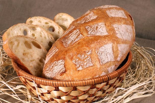 スライスした白パンは、テーブルクロスの灰色のリネンのストローバスケットに入っています