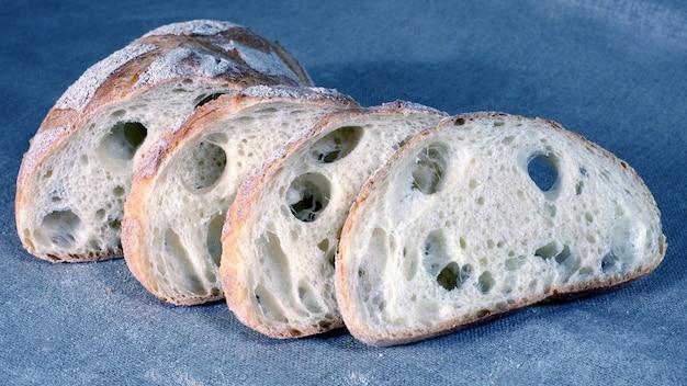 灰色のリネンのテーブルクロスの上に横たわっているスライスされた白パン。シリアルフード