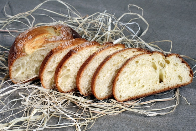 Sliced white bread lying in straw on grey linen tablecloth
