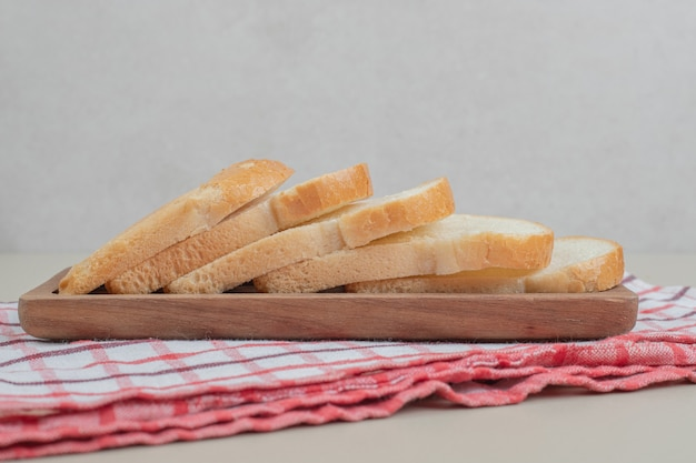 Нарезанный белый хлеб на деревянной доске. фото высокого качества