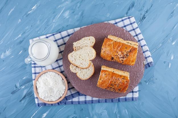 ミルクのガラスピッチャーと小麦粉の木製ボウルで白パンをスライスしました。