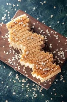 Fette di pane bianco con semi su tavola di legno