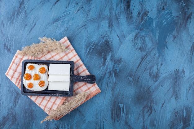 Fette di formaggio bianco e pane con panna e marmellata sul tagliere.