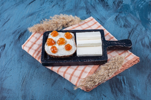Sliced white cheese and bread with cream and jam on cutting board