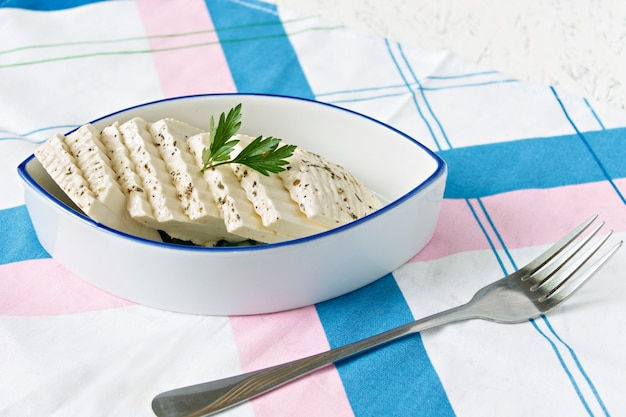 Sliced white cheese in a plate on a serviette and fork