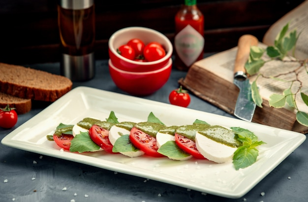 Sliced white cheese and tomato in leaves