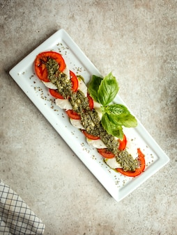 Sliced white cheese and tomato with herbs