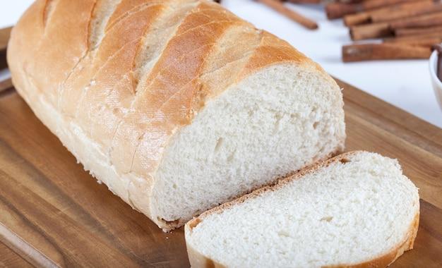 Нарезанный белый хлеб со специями на белом кухонном столе
