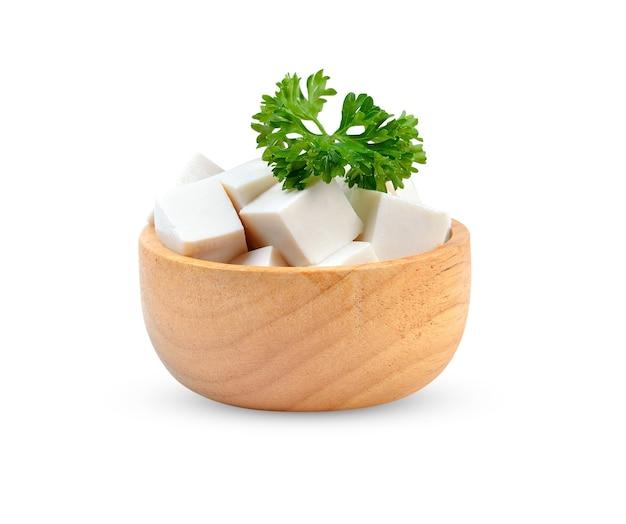 白い背景の上の木製のボウルに白い豆腐をスライスしました。