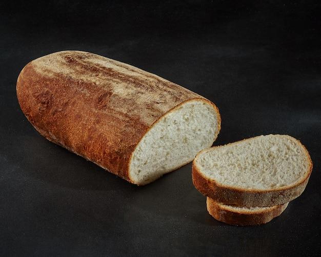 黒の背景にスライスした白パンのパン