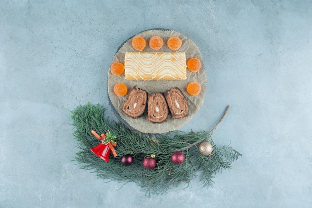 Rotolo di torta a fette e intero con marmellate su un vassoio con un ramo di pino decorato su marmo.