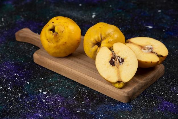 Frutti di mele cotogne fresche affettate e intere su tavola di legno.