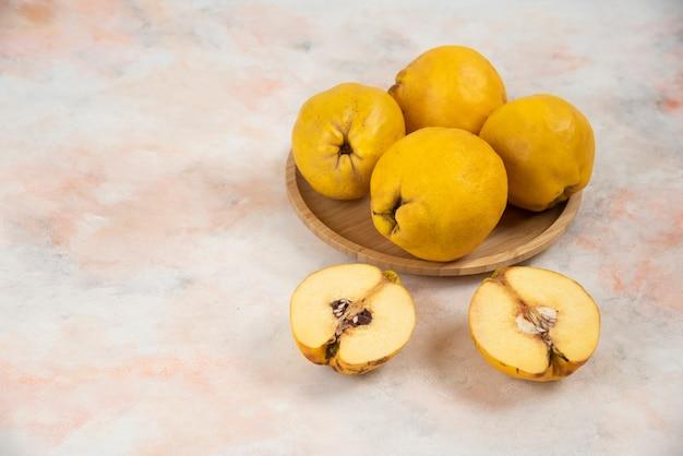 Frutti di mele cotogne fresche affettate e intere sul piatto di legno.