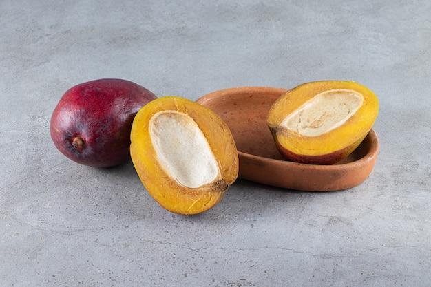 Sliced and whole fresh ripe mango fruits placed on stone table .