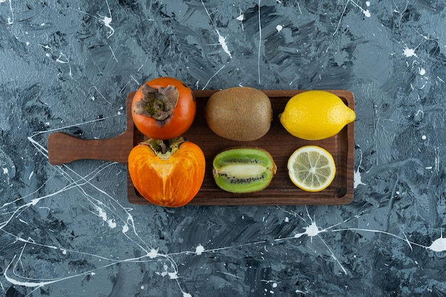 Sliced and whole fruits placed on a wooden board .