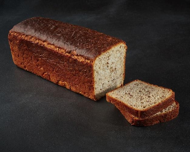 黒の背景に亜麻仁とスライスした全粒粉パン