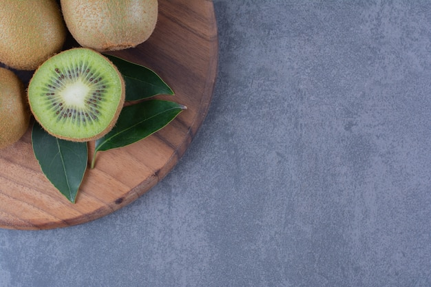 Sliced and whole kiwi fruits on board on the dark surface