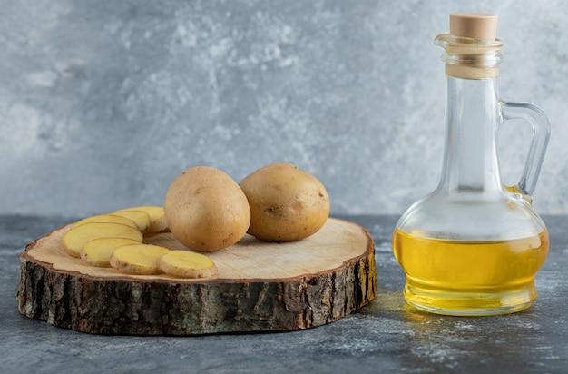 Patate a fette e intere su tavola di legno con olio.