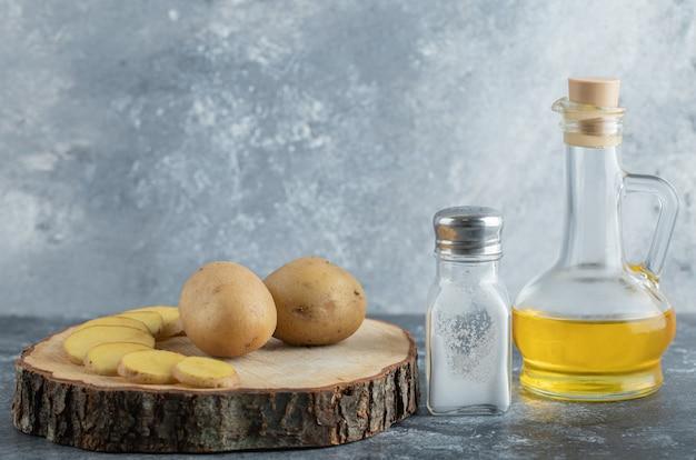 Patate a fette e intere su tavola di legno con sale e olio.