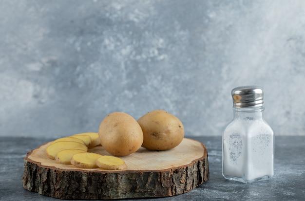 Patate a fette e intere su tavola di legno con sale.