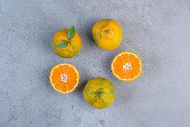 Mandarini affettati e interi disposti su fondo di marmo.