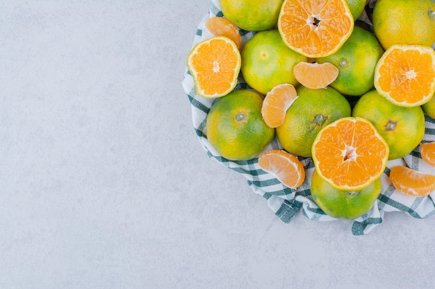 Sliced and whole tangerines in tablecloth on white background . high quality photo