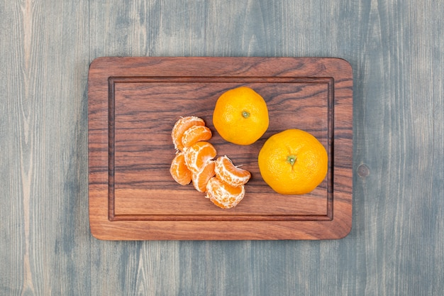 Sliced and whole tangerines on a wooden cutting board