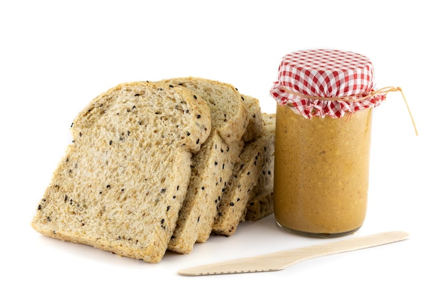 Sliced whole wheat bread and peanut butter. isolated on white background