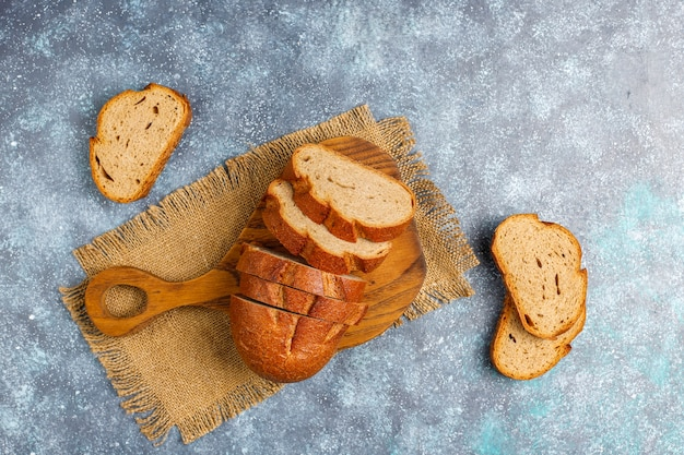 Sliced wholegrain bread on cutting board,top view