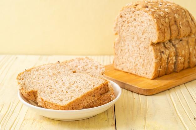 木製のテーブルで全粒パンをスライス