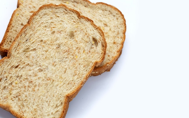Нарезанный цельнозерновой хлеб на белом фоне.
