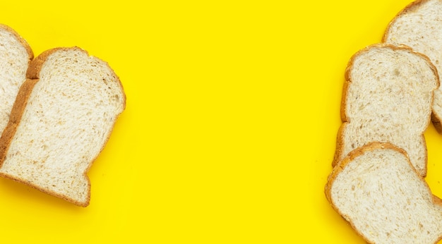 Нарезанный цельнозерновой хлеб на желтом фоне.