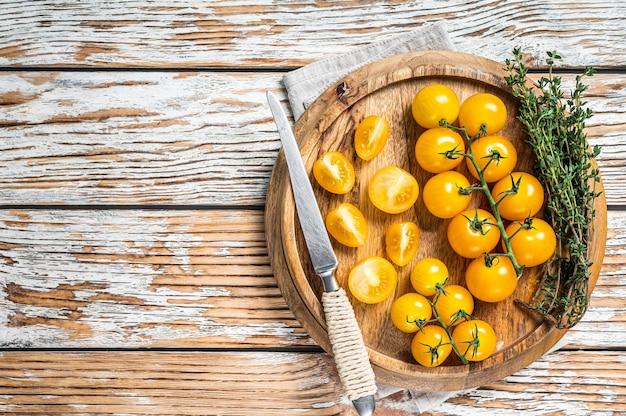 허브와 함께 나무 쟁반에 노란색 체리 토마토를 슬라이스. 흰색 나무 배경입니다. 평면도. 공간을 복사합니다.