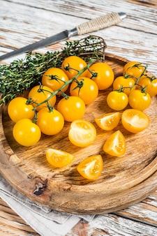 허브와 함께 나무 쟁반에 얇게 썬 노란색 체리 토마토. 흰색 나무 배경입니다. 평면도.