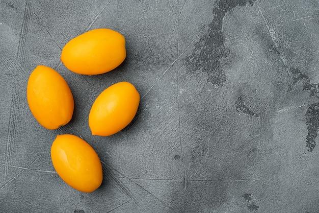 회색 돌 테이블 배경에 얇게 썬 노란색 체리 토마토 세트, 텍스트 복사 공간이 있는 평면도