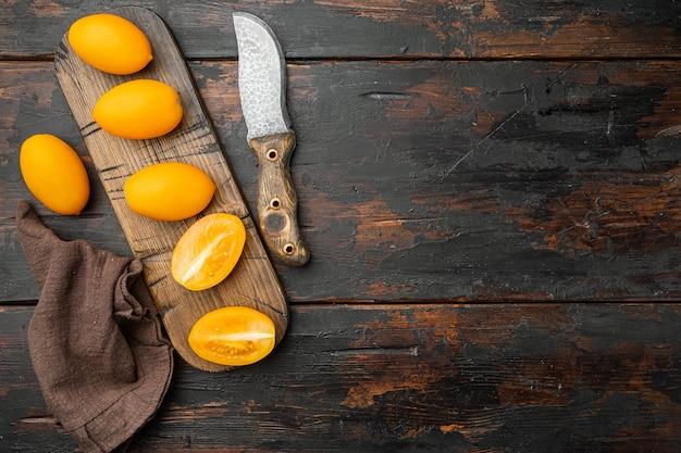 오래된 어두운 나무 테이블 배경에 얇게 썬 노란색 체리 토마토 세트, 텍스트 복사 공간이 있는 평면도