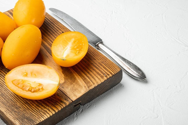 Набор нарезанных желтых помидоров черри на фоне белого каменного стола с местом для текста