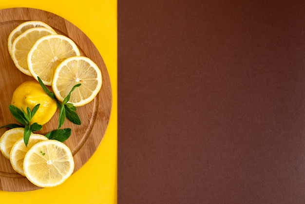 Sliced yellow lemons on a brown wooden board, next to it lies a bunch of green mint, summer drinks