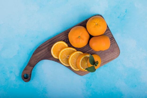 Нарезанные желтые апельсины на деревянном блюде, вид сверху.