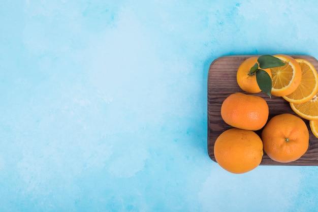 나무 접시에 노란색 오렌지를 슬라이스.