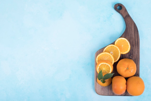 Нарезанные желтые апельсины на деревянном блюде.