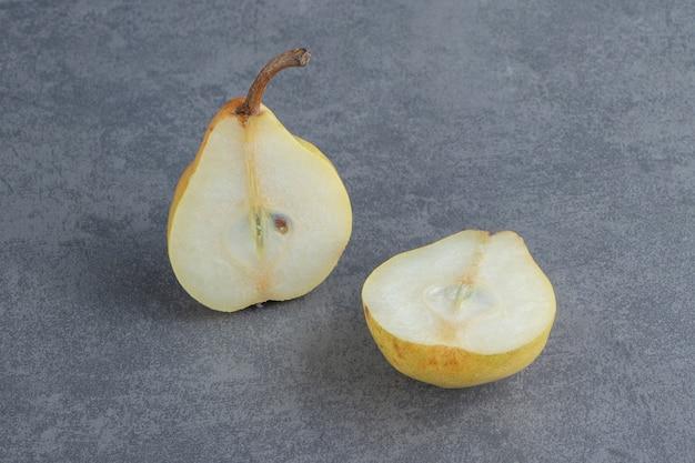 Pera gialla affettata isolata sulla superficie grigia