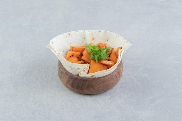 Zucchine a fette su lavash, nella ciotola, sul fondo di marmo.