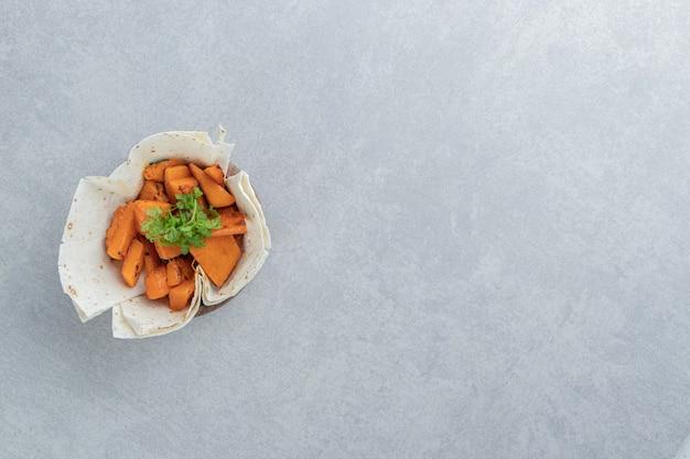 Zucchine a fette su lavash, nella ciotola, sul marmo.