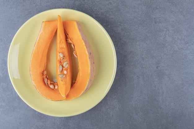 スライスしたズッキーニをお皿の上、大理石の表面に。